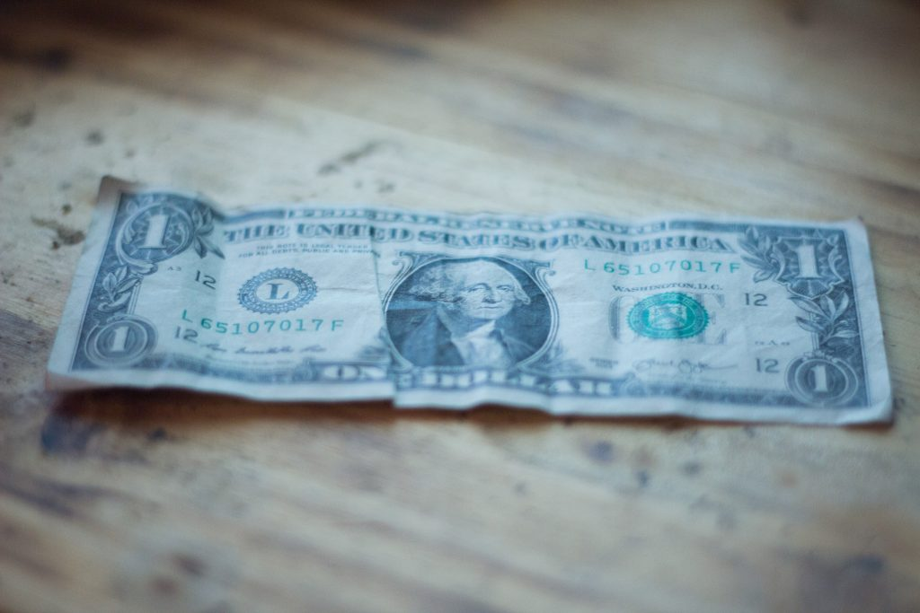 Dollar Bill On Wooden Desk -- JackHarner @ Unsplash